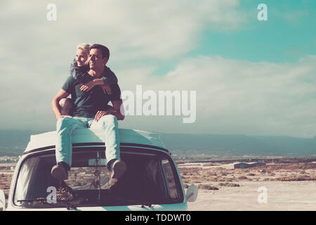 Travel people concept with young couple of man and woman sitting on the roof of old vintage van - love and relationship for travelers - beautiful land - Stock Image