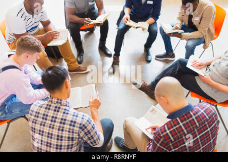 Men reading and discussing bible in prayer group - Stock Image
