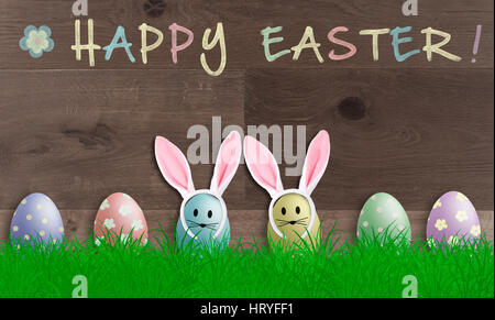 colorful pastel easter eggs with bunny ears on wooden background, promotional sign with text happy easter - Stock Image