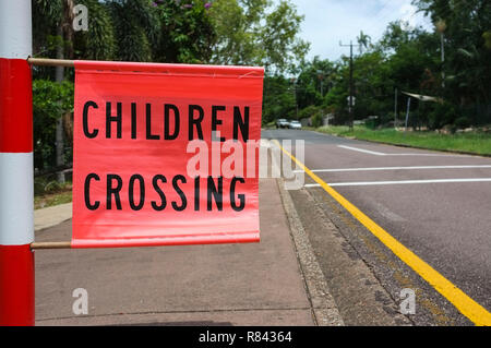 Children crossing flag along a road in a school zone, in Darwin, Australia. - Stock Image