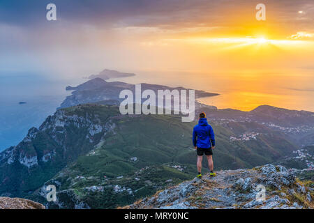 San Michele mountain, Pimonte, Napoli, Campania, Italy. Sunset over Sorrento peninsula and Capri island. A hiker admires the view - Stock Image