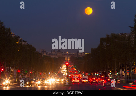 The moon rising above Avenue des Champs Elysees looking towards Louvre Paris France - Stock Image