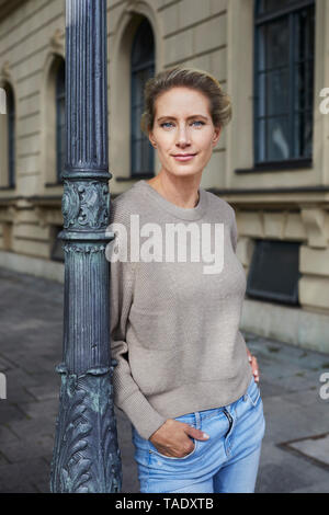 Portrait of confident woman leaning against lamp post in the city - Stock Image