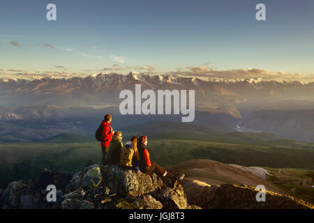Friends on mountain top looking to sunset - Stock Image