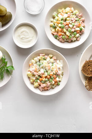 Tasty salad 'Olivier' from boiled vegetables and sausage with mayonnaise in bowl. Russian New Year or Christmas salad on light background with copy sp - Stock Image