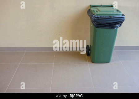 One wheelie bin against a wall - Stock Image