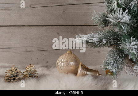 beautifull still life of Christmas ornaments and tree covered with snow, on sheepskin and old vintage wooden background - Stock Image