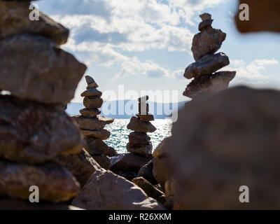 Stack of rocks on beach against light - Stock Image