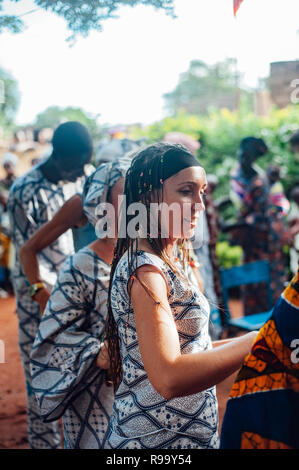Young caucasian woman singing and dancing. Multi Ethnic music party to celebrate western and developing countries cooperation. Bamako, Mali. Africa - Stock Image