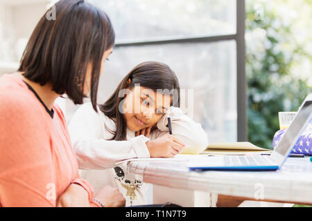 Mother at laptop watching daughter doing homework at table - Stock Image