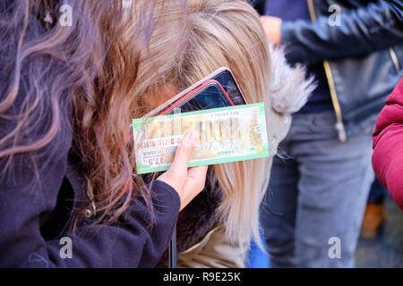 Istanbul, Turkey  Thousands wait in line to buy ticket for the Turkish national lottery's New Year's eve draw some waiting over 3 hours from the Nimet Abla in Eminonu Square, an annual tradition due to believed lucky nature of the establishment.  This lady leaves with ticket in hand. - Stock Image