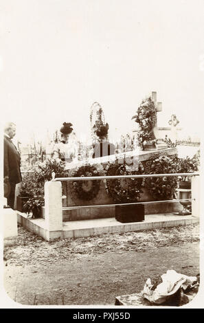 Two women and a gentleman pay their respects beside the grave of a recently deceased relative      Date: 1899 - Stock Image