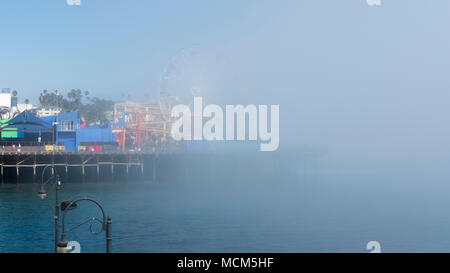 Peculiar weather with sudden, fast fog drifting from Venice Beach towards the iconic ferris wheel at Santa Monica Pier, Los Angeles, California, USA - Stock Image