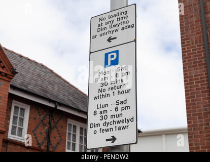 Bilingual street sign in English and Welsh indicating loading and parking restrictions Wrexham Wales June 2018 - Stock Image