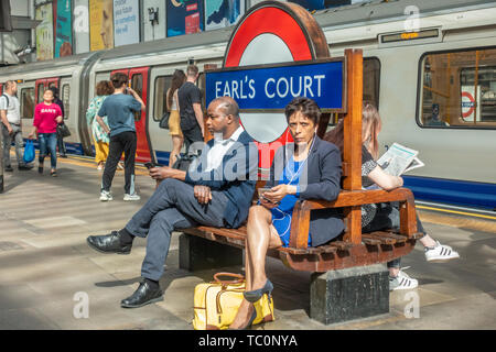 People sit on a bench on the platform at Earl's Court London Underground Station - Stock Image
