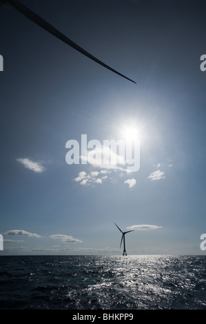 image of offshore wind turbines with sun behind cloud - Stock Image