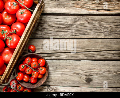 Ripe tomatoes in a wooden box. On a wooden table. - Stock Image