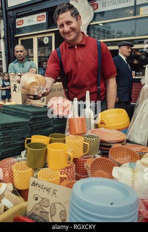 Market trader on Roman Road, Bethnal Green, London England,UK, 1974 Rodney the Plastics Man. - Stock Image