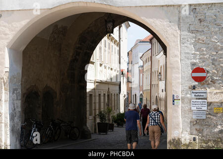 Tourists making their way through the Linzer Tor (or Brückentor) in Stein, the gateway into Stein an der Donau - Stock Image