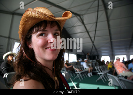 Portrait of woman at a music festival wearing straw cowboy hat - Stock Image