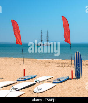 Standup Paddle boards on beach with bokeh caravel in background. - Stock Image