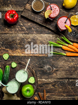 Healthy smoothies with fruits and vegetables. On a wooden background. - Stock Image