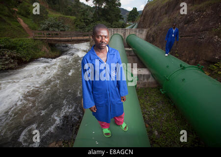 Technicians inspecting pipes carrying water to hydro electric powerplant, Rwanda - Stock Image