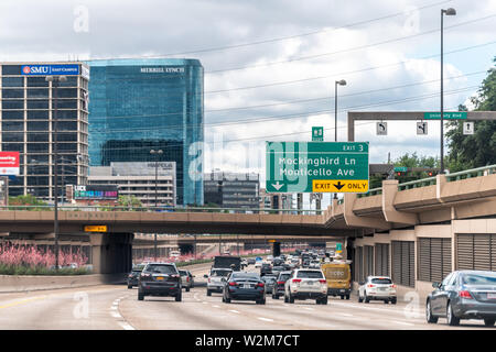 Dallas, USA - June 7, 2019: Highway 75 in city in summer with cars in traffic with signs for SMY and Merrill Lynch and exit for downtown - Stock Image