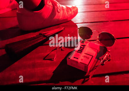 A clubbers fan, cigarettes, sunglasses and lighter at a club in Ibiza - Stock Image