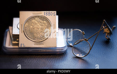 Coin Collector Desk with stack of coins featuring a beautiful mint state Morgan Dollar and magnifier glass. - Stock Image