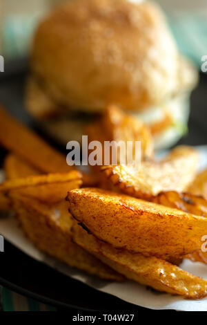 Plate of tasty hand cut fried to perfection chips fries with beef burger in bread bun. - Stock Image