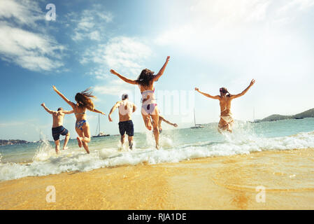 Big group of friends runs at sea beach. Tropical vacations concept - Stock Image