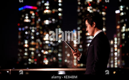 Side view portrait of businessman using smartphone against night view of city - Stock Image