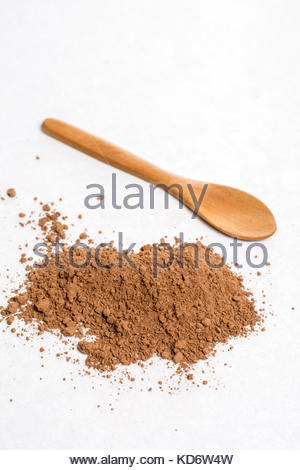 Flat lay above brown cocoa powder with wooden spoon on the white marble background. - Stock Image