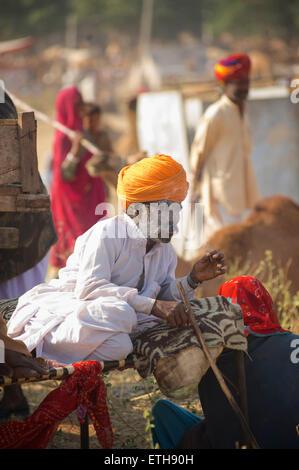 Rajasthani man in distinctive white attire and orange turban, smoking. Pushkar, Rajasthan, India - Stock Image