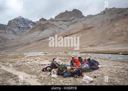 Tibetan nomad family sitting on ground near Lha Chu river en route Mount kailash kora - Stock Image