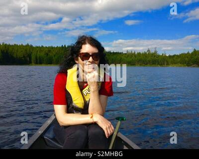 Brunette woman in a canoe on a lake in Fundy National Park Canada - Stock Image