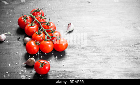 Ripe tomatoes with garlic and salt. On black background. - Stock Image