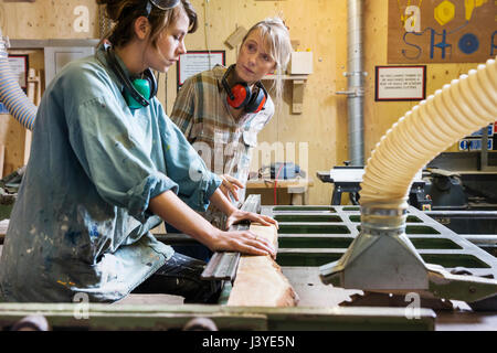 Two women talking and using machinery in a wood workshop - Stock Image