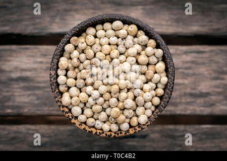 organic kampot dried white pepper corns in cambodia in traditonal asian wood bowl - Stock Image