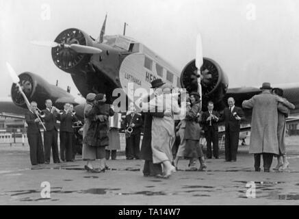 On April 1, 1937, Lufthansa published this photo as an April Fools' joke with the message that from then on a music band would perform before each flight, similar to passenger ships. Here, dancing passengers in front of a Junkers Ju 52 / 3m. - Stock Image