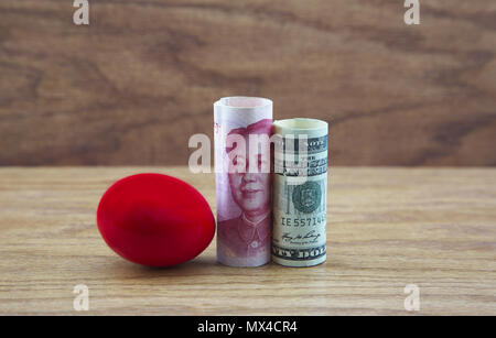 Crimson nest egg placed with Chinese and American currency reflects a risky investment environment. - Stock Image