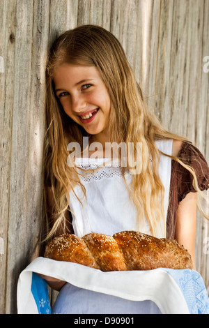 Smiling girl leaning against fence, holding loaf of twisted bread - Stock Image