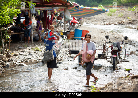 Hanunoo Mangyan women cross a shallow creek with their children at a Mangyan market in Mansalay, Oriental Mindoro, Philippines. - Stock Image