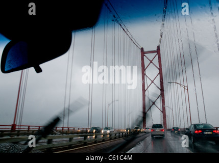Vehicles travelling over the Ponte 25 de Abril in Lisbon, Portugal during a rainstorm - Stock Image