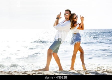 Happy couple beach sea fun - Stock Image
