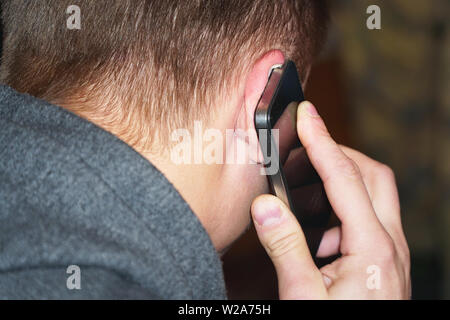 A man talking on the phone. The phone is at the man's ear - Stock Image