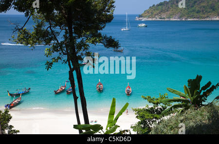 View over iconic tropical beach at 'Paradise Beach' from above with longtail boats and people on the beach - Stock Image