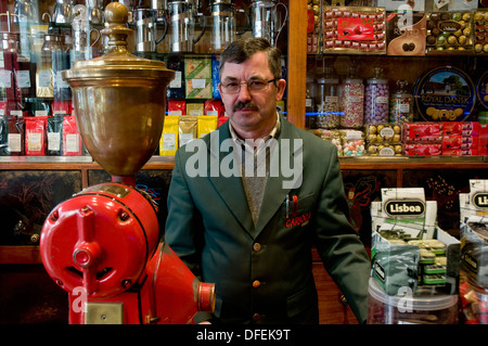 A shopkeeper surrounded by his wares at A Carioca, a coffee store in Chiado, Lisbon, Portugal.  - Stock Image