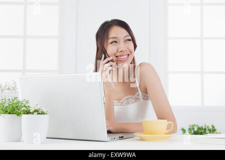 Young woman looking away with smile and on the phone, - Stock Image